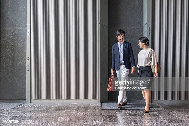 Japanese Businessman and Businesswoman Exiting Elevator in Modern Office Building