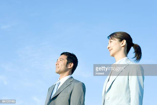 Japanese businessman and woman looking away