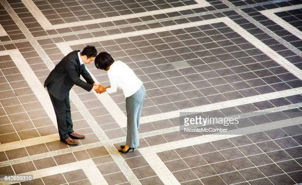 japanese businessman bowing as he handshakes female colleague - humility stock pictures, royalty-free photos & images