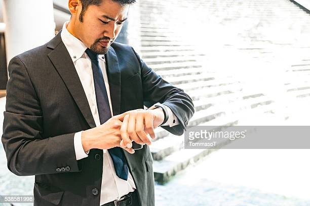Japanese businessman checking his smart watch