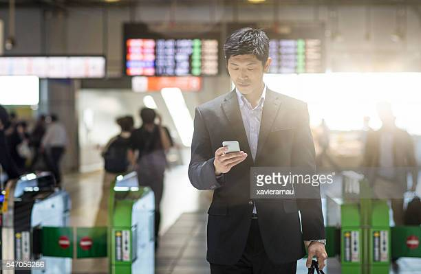 Japanese businessman checking the mobile phone at the station