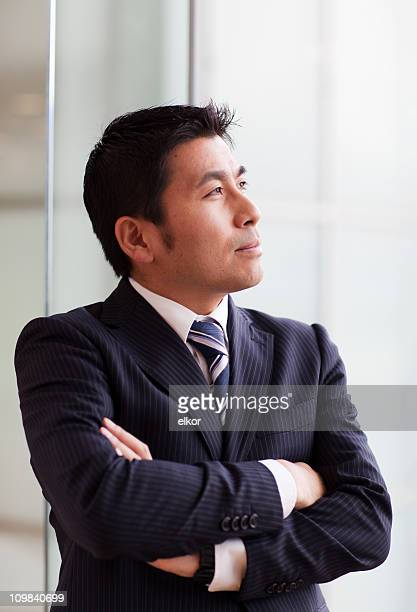 Japanese businessman contemplating at the window