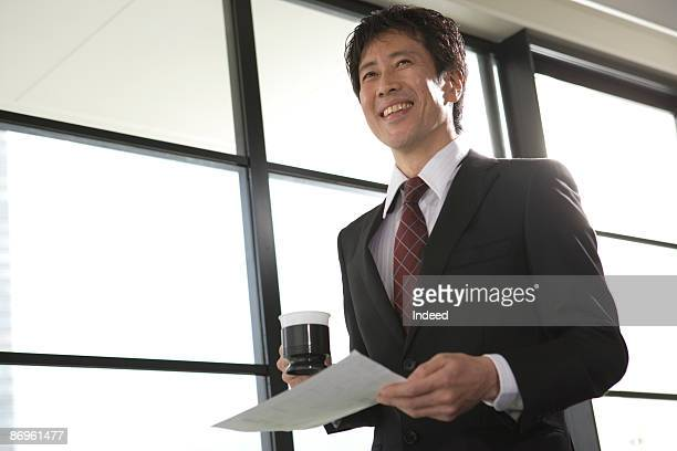 Japanese businessman having coffee, smiling