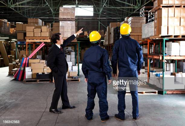 japanese businessman in a warehouse - black jumpsuit stock pictures, royalty-free photos & images