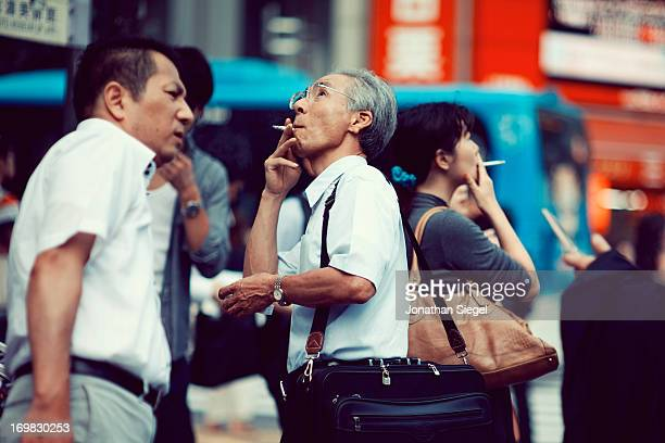 Japanese businessman, in the middle of a crowd, smoking outside and looking up to the sky.