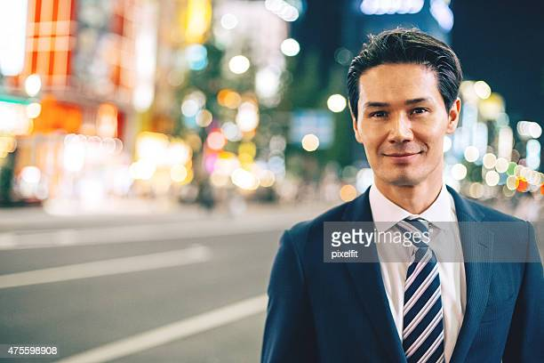 Japanese businessman in Tokyo at night outdoors