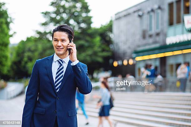 Japanese businessman in Tokyo talking on the phone outdoors