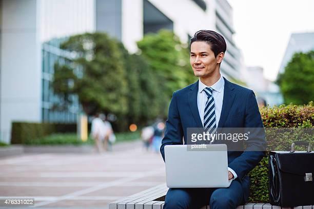 Japanischen Geschäftsmann in Tokio mit computer im Freien