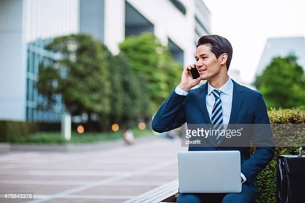 東京で日本のビジネスマン、電話とコンピューターの屋外