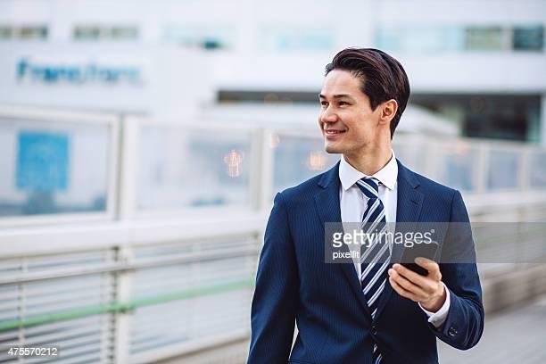 東京で日本のビジネスマン、スマートフォン、屋外でのリラクゼーション