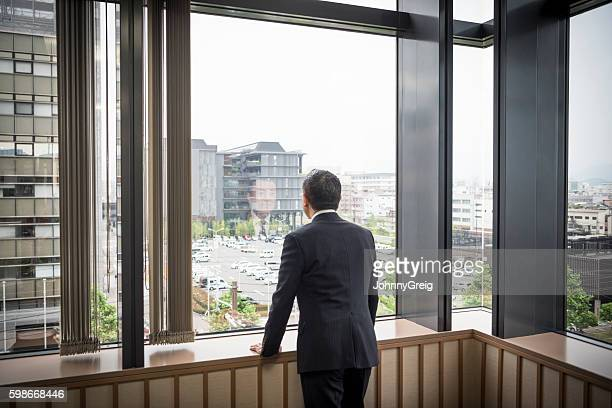 Japanese businessman leaning on window sill looking at view