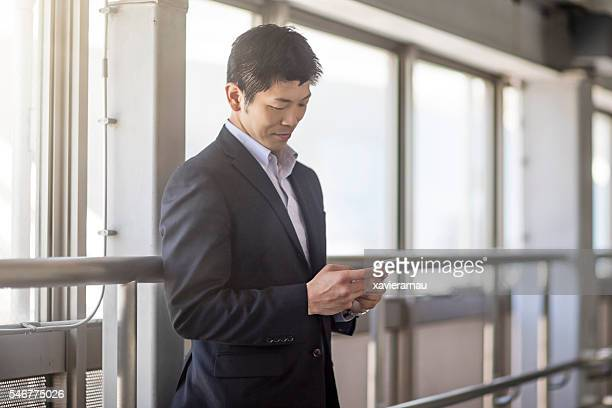 Japanese businessman looking at his phone at the station