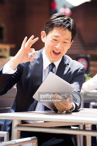 日本のビジネスマンが優れたサインを屋外のタブレットでのコンファレンス