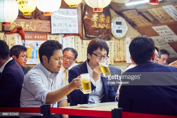 Japanese businessman often known as salarymen enjoy an after work beer in a barbecue restaurant in Ginza There's often an obligation to socialize...