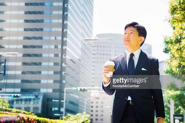 日本のビジネスマンに彼の途中、コーヒー
