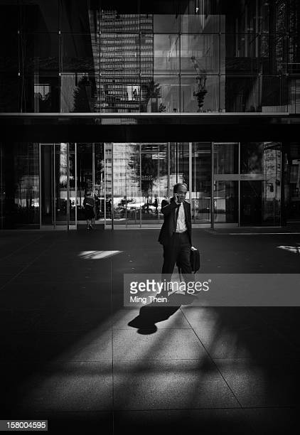 Japanese businessman on telephone exiting an office silhouetted in shadow in downtown Tokyo