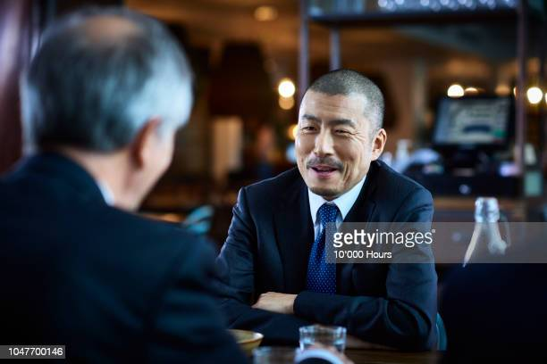 japanese businessman sitting opposite male coworker in restaurant - two people ストックフォトと画像