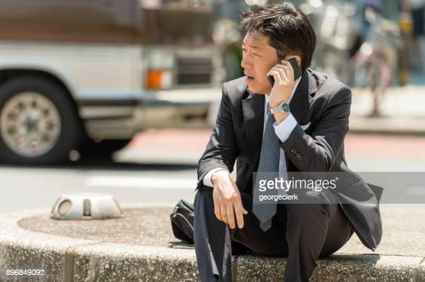 呼び出しを行うに座っている日本のビジネスマン