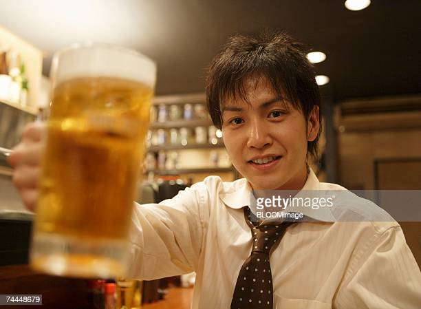 Japanese businessman smiling with holding a glass of beer
