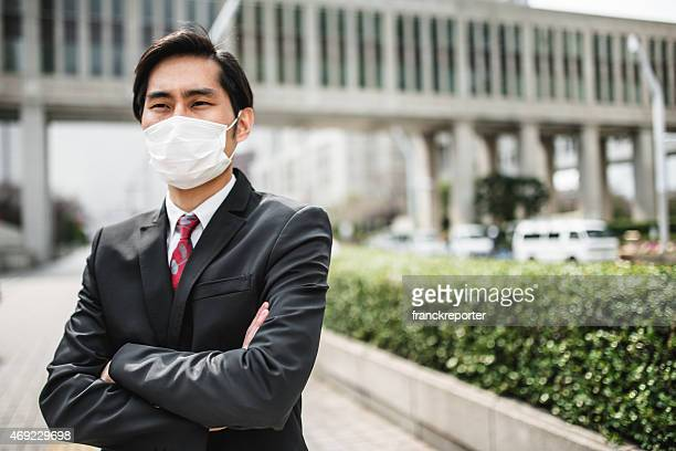 japanese businessman standing on the city with a pollution mask - epidemi bildbanksfoton och bilder