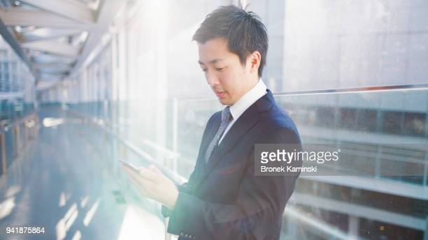 a japanese businessman uses a mobile phone - ビジネスマン ストックフォトと画像