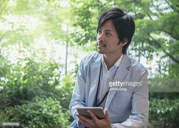 Japanese businessman using digital tablet looking away
