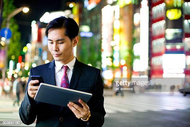 Hombre de negocios japonés con tableta digital, Tokyo.