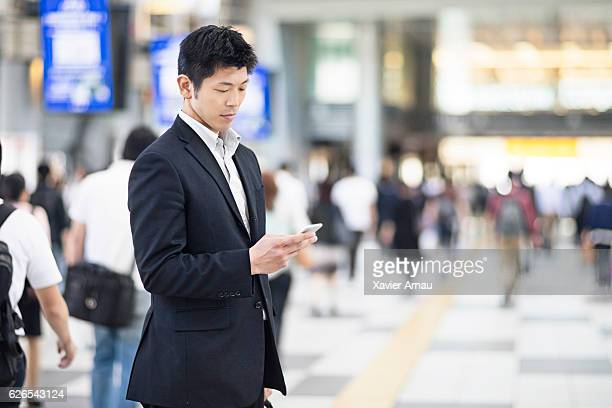 japanese businessman using mobile phone at the station - east asian culture stock photos and pictures