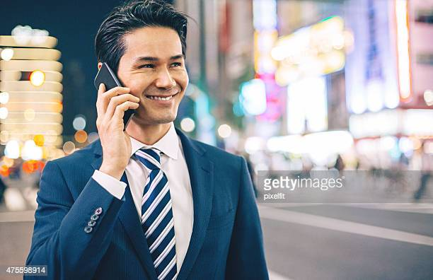 Japanese businessman using phone in Tokyo at night outdoors