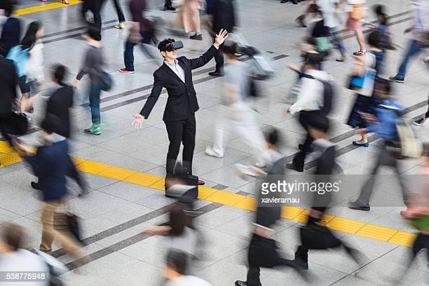 Japanese businessman using VR glasses in the street
