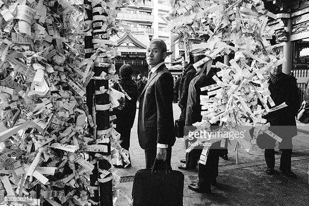 A Japanese businessman waiting for his coworker to pray for prosperity of their firms during a New Year's ceremony at Kanda Myojin Shrine in downtown...