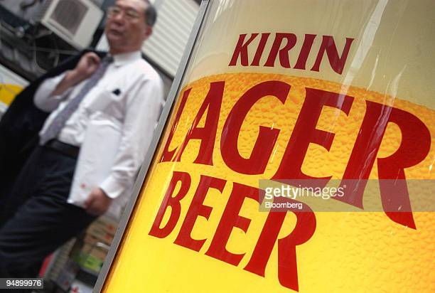 Japanese businessman walks past a Kirin Lager sign outside a local watering hole in Tokyo Thursday August 5 2004 Shares of Kirin Brewery Co Japan's...