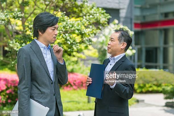 Japanese businessmen discussing work in a garden
