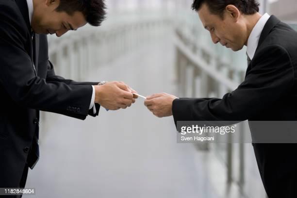 japanese businessmen exchanging business cards - 交換する ストックフォトと画像