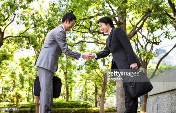 japanse zakenlieden elkaar groeten - social grace stockfoto's en -beelden