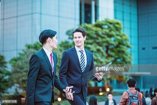 Japanese businessmen in Tokyo having a conversation outdoors
