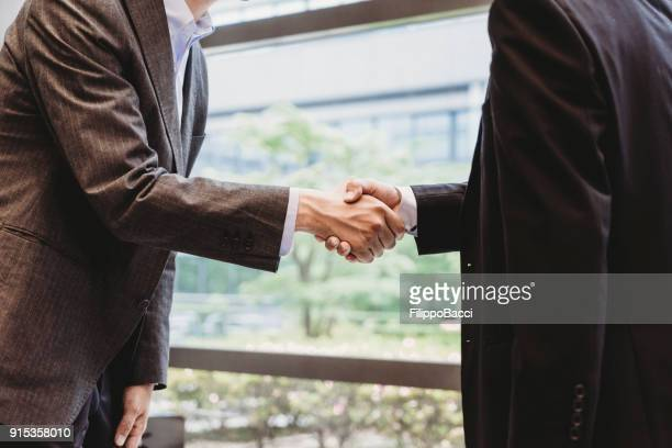 japanese businessmen shaking hands - ambassador stock pictures, royalty-free photos & images