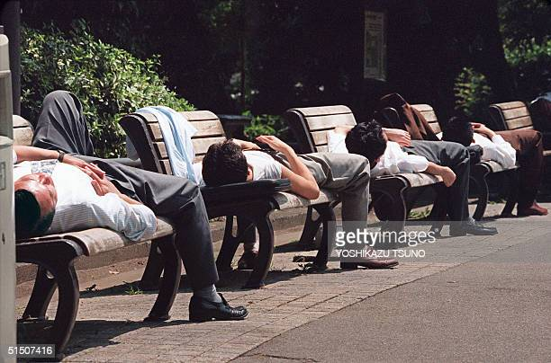 Japanese businessmen take naps on benches in Hibiya park central Tokyo 04 August 1994