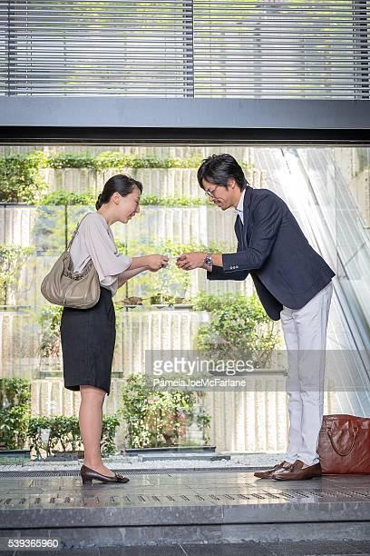日本の女性実業家と実業家名刺を手渡すオフィス内のロビー