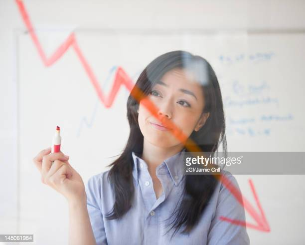 japanese businesswoman drawing red arrow - decline stock pictures, royalty-free photos & images