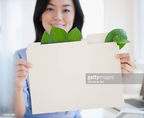 Japanese businesswoman holding folder containing leaves