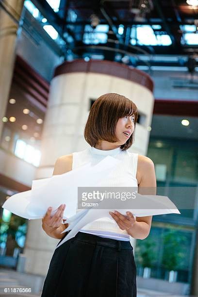 japanese businesswoman lost in paperwork