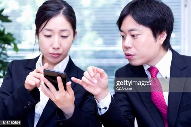 クライアントからのメールの彼女の同僚を示す日本の実業家