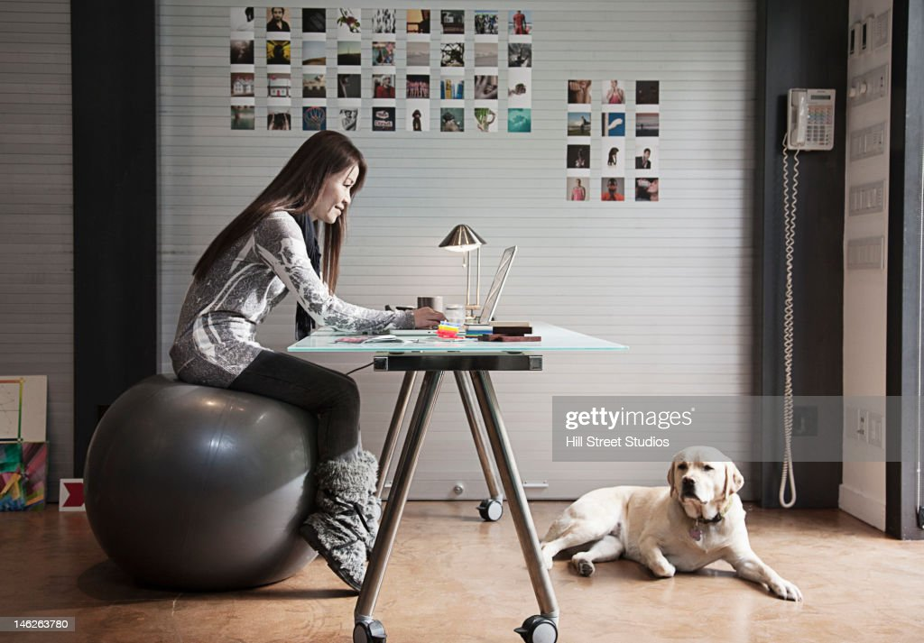 Japanese businesswoman sitting on exercise ball and working at desk : Stock Photo
