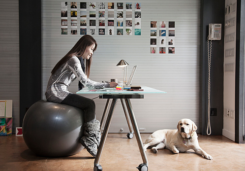 Japanese businesswoman sitting on exercise ball and working at desk - gettyimageskorea