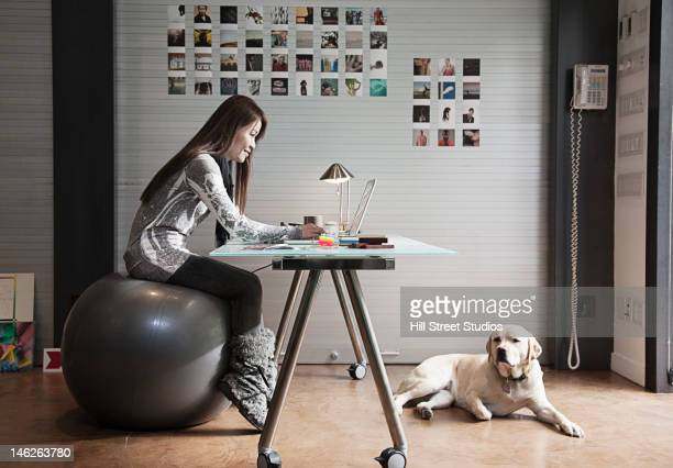 japanese businesswoman sitting on exercise ball and working at desk - fitness ball stock pictures, royalty-free photos & images