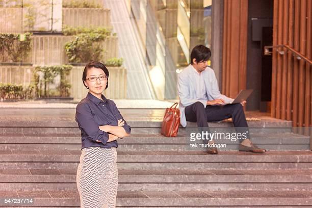 Japanische Geschäftsfrau stehend vor männlichen Kollegen im kyoto, japan
