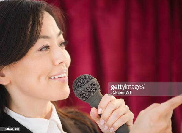 Japanese businesswoman talking into microphone
