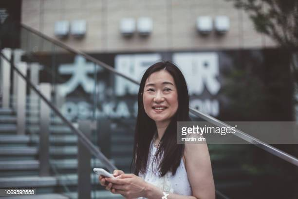 japanese businesswoman texting outside - candid forum stock pictures, royalty-free photos & images