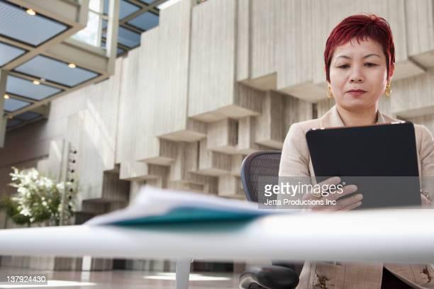 日本のデジタルタブレットを使用してビジネスウーマン - focus on background ストックフォトと画像